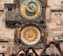Tourists taking photos of old astronomical clock in the center square of Prague.