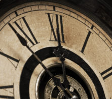A Close-up of the face of an antique grandfather clock that is going to strike midnight shortly